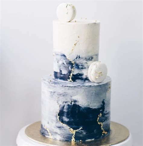 an ombre blue buttercream wedding cake with gold leaf